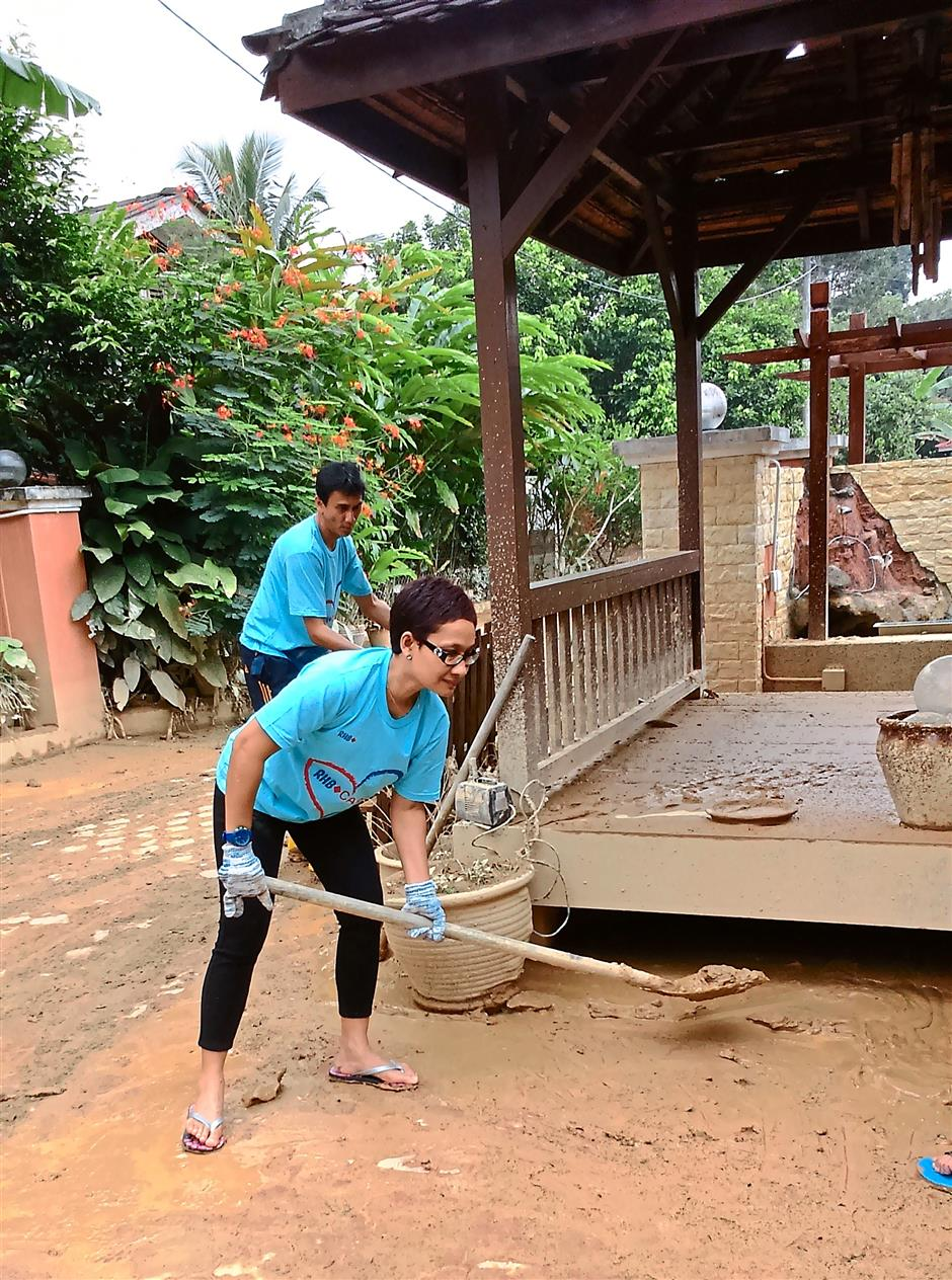 Helping out: RHB staff volunteers cleaning up a house affected by the floods.