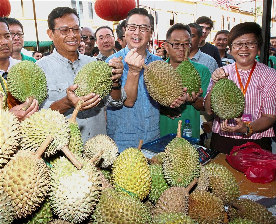 All-time favourite: Ahmad Shabery (left), Liow and Chew (in pink) checking out the durians at the 2017 Malaysia International Durian Cultural Tourism Festival in Bentong.