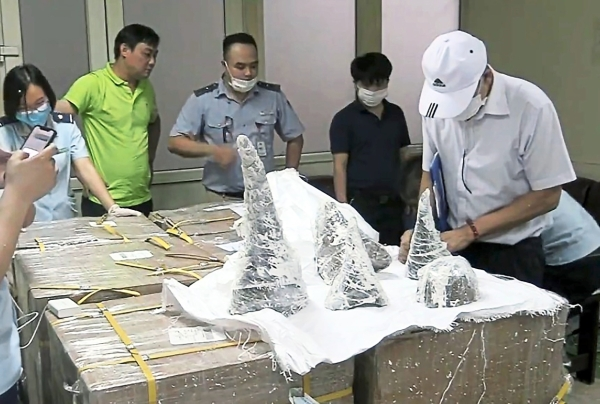 Cracking the case: Officials at Hanoiu2019s Noi Bai International Airport removing the smuggled rhino horn pieces from their packaging after breaking them out of plaster casts. u2014 AFP