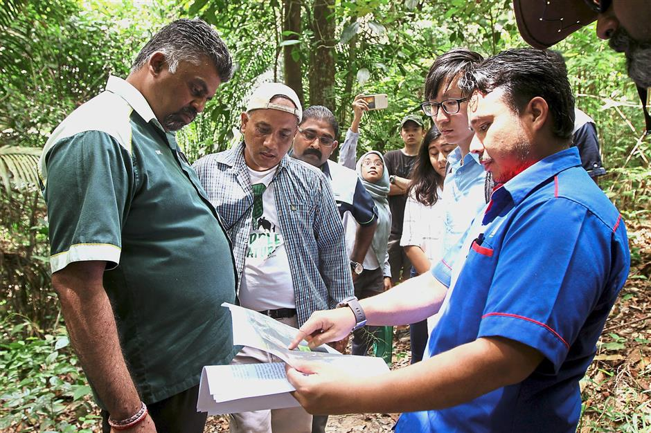 Residents and NGOs leading media personnel to view the damage in Bukit Cerakah.