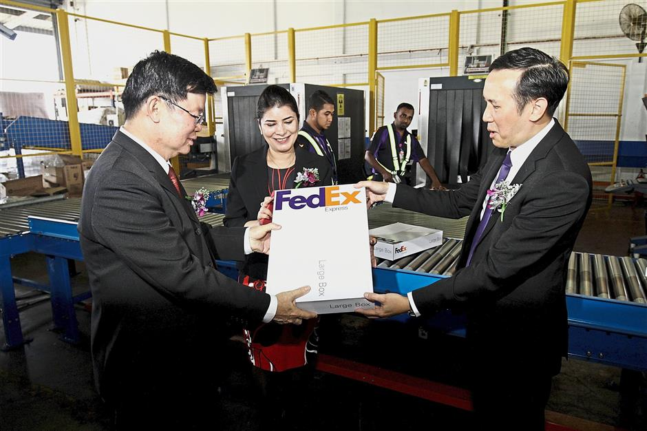 Chong (right) showing a parcel to Chow during the launch of the Penang Gateway facility at MAB New Cargo Complex at Penang International Airport. With them is Kawal.