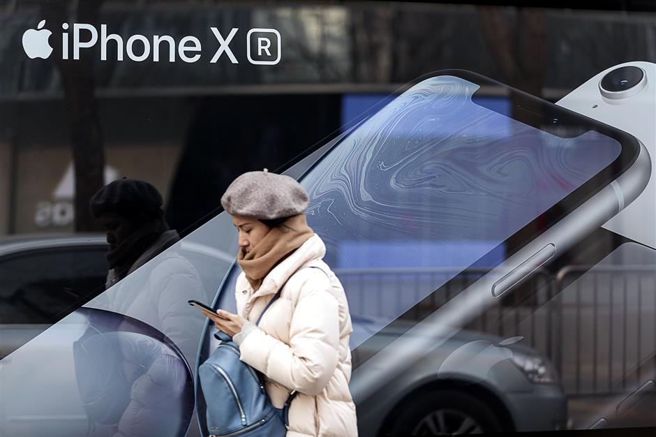 A woman looks at a smartphone while walking past an advertisement for the Apple Inc. iPhone XR in Beijing, China, on Thursday, Jan. 3, 2019. Appleu00a0cut its revenue outlook for the first time in almost two decades citing weaker demand in China, triggering a slump for Asian suppliers and a wave of lower price targets on Wall Street. Photographer: Shawn Koh/Bloomberg