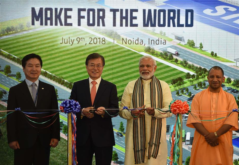 CORRECTION - South Korea\'s President Moon Jae-in (2L), India\'s Prime Minister Narendra Modi (2R) and Chief Minister of Uttar Pradesh state Yogi Adityanath (R) pose for a picture during the inauguration of the world\'s largest mobile factory at the Samsung India electronics private limited in Noida on July 9, 2018. Samsung has opened the world\'s largest smartphone factory in India, a move Prime Minister Narendra Modi said July 9 would help transform Asia\'s third-largest economy into a manufacturing hub. / AFP PHOTO / MONEY SHARMA / u201cThe erroneous mention[s] appearing in the metadata of this photo by MONEY SHARMA has been modified in AFP systems in the following manner: [South Korea\'s President] instead of [South Korea Prime Minister]. Please immediately remove the erroneous mention[s] from all your online services and delete it (them) from your servers. If you have been authorized by AFP to distribute it (them) to third parties, please ensure that the same actions are carried out by them. Failure to promptly comply with these instructions will entail liability on your part for any continued or post notification usage. Therefore we thank you very much for all your attention and prompt action. We are sorry for the inconvenience this notification may cause and remain at your disposal for any further information you may require.u201d