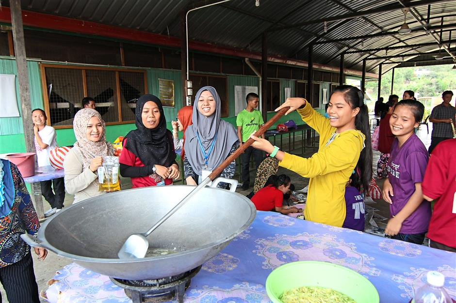Time for a meal: UM students cooking lunch during the gotong-royong to feed the other hungry volunteers.