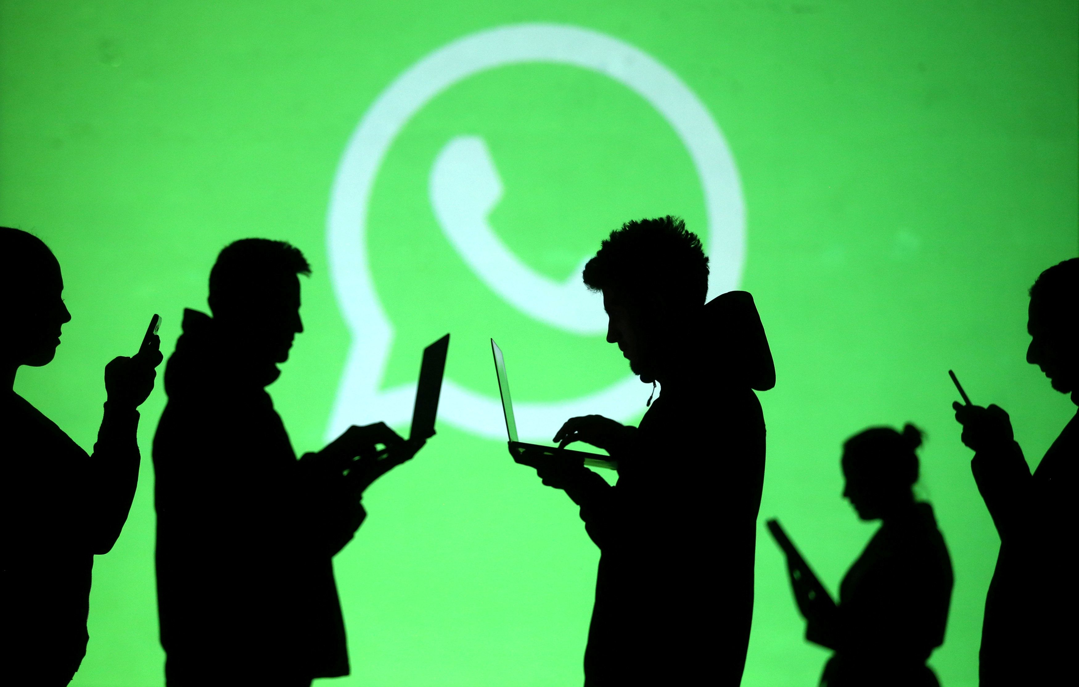 REFILE - CLARIFYING CAPTION Silhouettes of laptop and mobile device users are seen next to a screen projection of Whatsapp logo in this picture illustration taken March 28, 2018. REUTERS/Dado Ruvic/Illustration