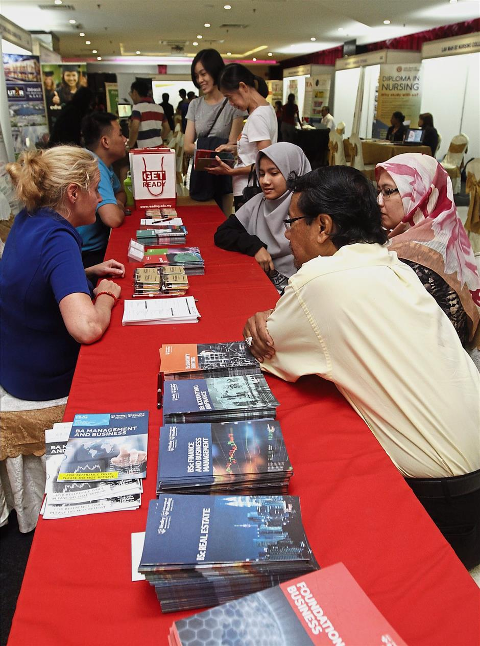Staff members from University of Reading Malaysia explaining their programmes to visitors.