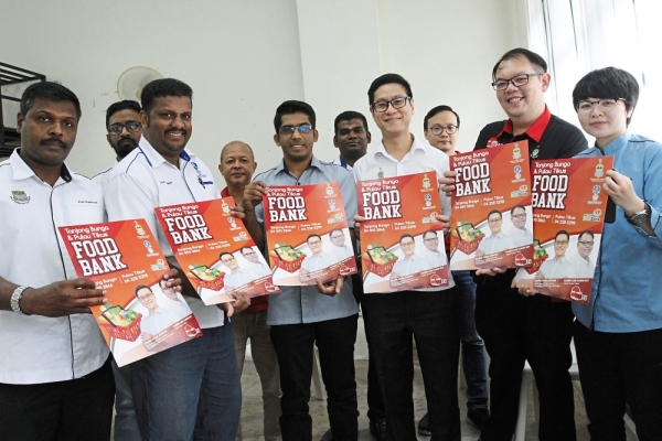 (Front row, from left) Kaliyappan, Tharman, Muhammad Shameer, Zairil, Lee and Tan holding posters announcing the food aid programme which will start next month for needy families living in Tanjung Bungah and Pulau Tikus.