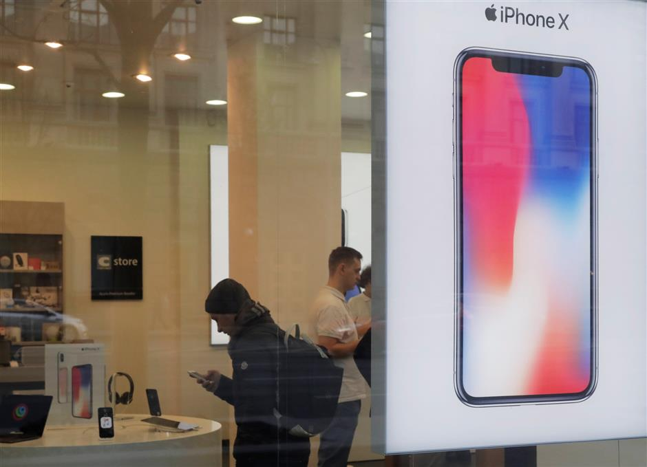 A customer is seen behind an Apple\'s new iPhone X advertisement board during its global launch at a cell phone store in central Moscow, Russia November 3, 2017. REUTERS/Tatyana  Makeyeva