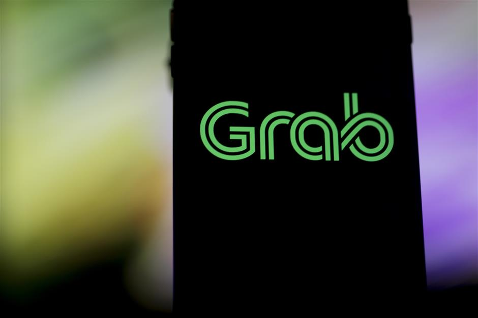 The Grab logo is displayed for a photograph on an Apple Inc. iPhone in Bangkok, Thailand, on Friday, March 9, 2018. Grab, the dominant ride-hailing service in Southeast Asia, is close to finalizing a deal to acquireu00a0Uberu00a0Technologies Inc.\'s business in the region and may sign a deal this week or next, according to people familiar with the matter. Photographer: Brent Lewin/Bloomberg