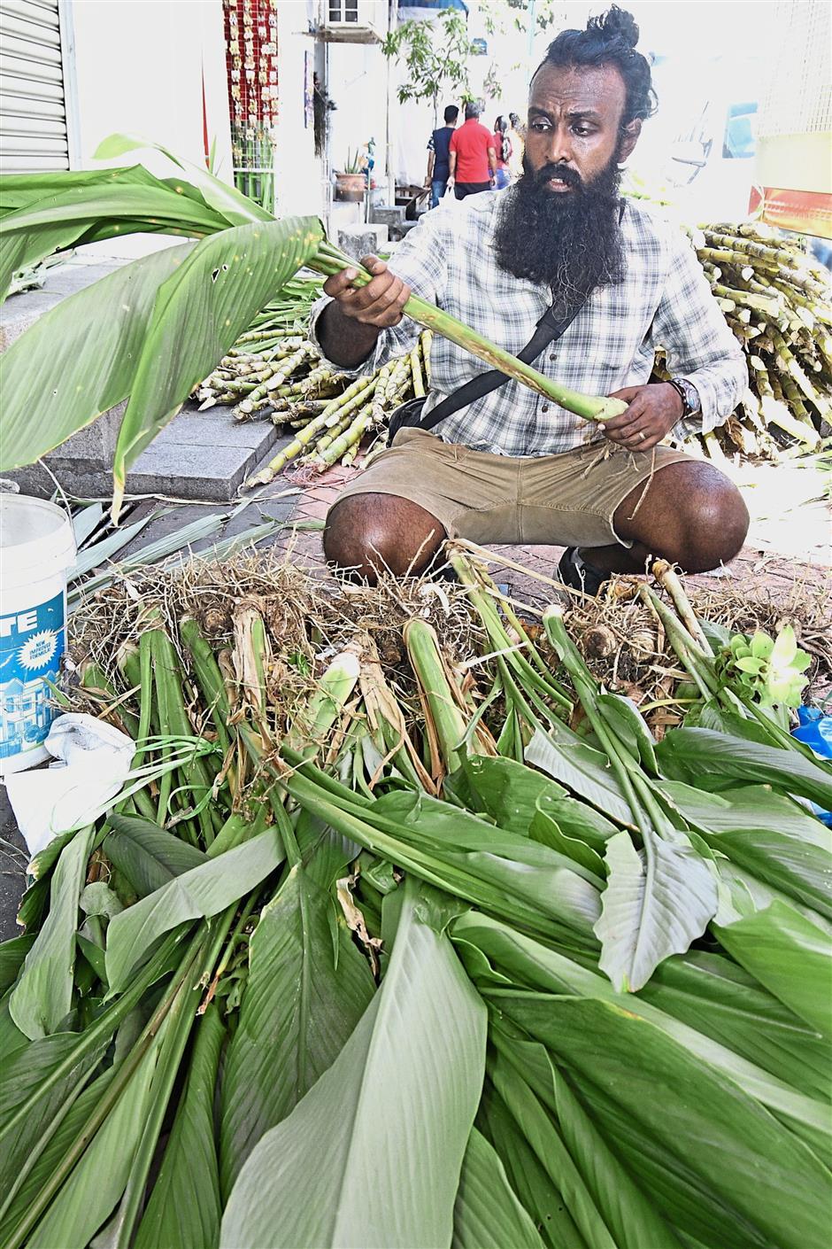 Anbukarasan Morotar preparing turmeric leaves in Little India while K. Rajathi (below) ties flower garlands at a shop along Jalan Mesjid Kapitan Keling. —Photos: CHAN BOON KAI, LIM BENG TATT/The Star and Bernama
