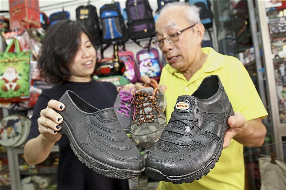 Various designs: Retired teacher Lee Yew Khoon (in yellow) and Lim comparing rubber shoes at Lee Sing Merchant in Noordin Street, Penang.