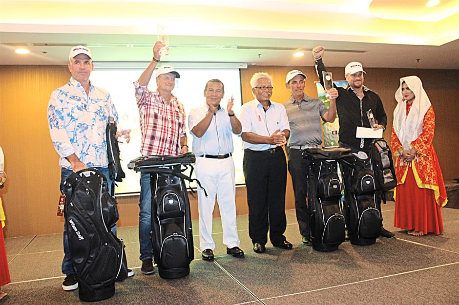 We've made it again: Jubilant Royal Harts golfers posing for a photo after receiving their prizes from Tourism Malaysia director Saidi Bundan (third left).