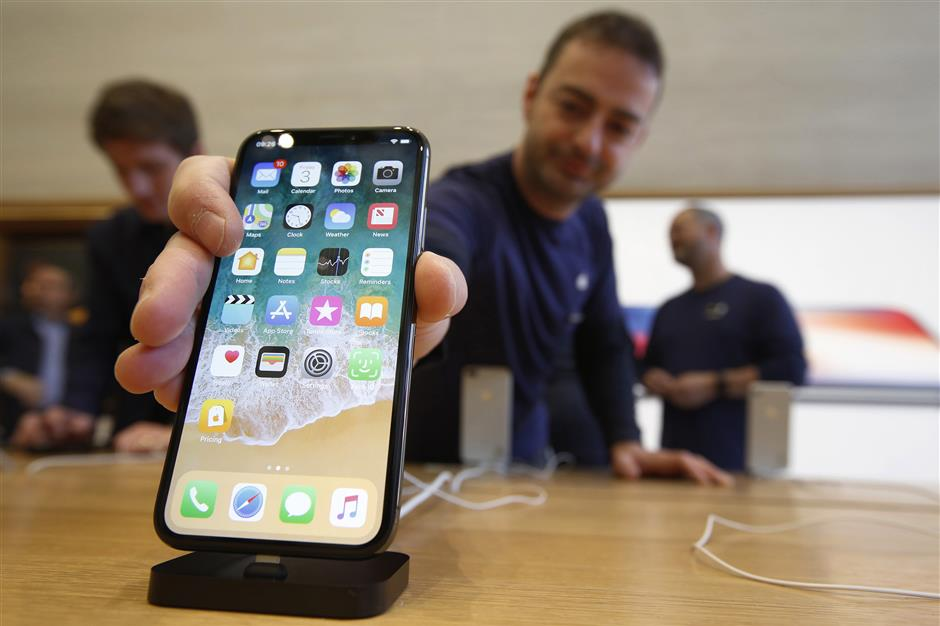 An employee adjusts an iPhone X smartphone on display at the Apple Inc. store on Regent Street in London, U.K., on Friday, Nov. 3, 2017. ??Supported by resurgent iPad and Mac sales, the 10-year anniversary iPhone will help push revenue to a record high of $84 billion to $87 billion in the quarter ending in late December, Apple said in a statement. Photographer: Luke MacGregor/Bloomberg