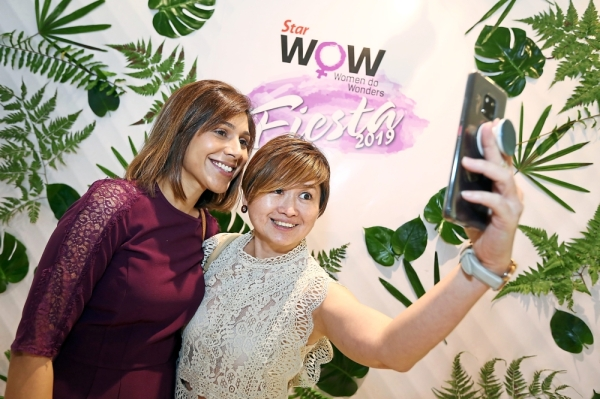 Dr. Saritha Dharan (left) and Jennifer Koay taking a wefie at the photo booth on the first day of the fiesta.