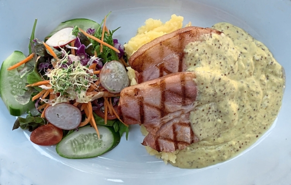 The Pork Bacon Steak is served with double mustard hollandaise sauce.