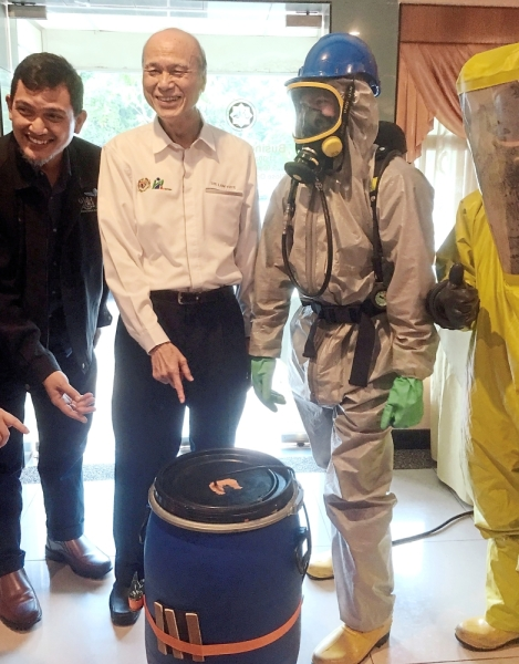 Lee (middle) posing with a barrel of chemicals at the Major Chemical Spill and Leak Response CSR Session programme at TS Hotel.