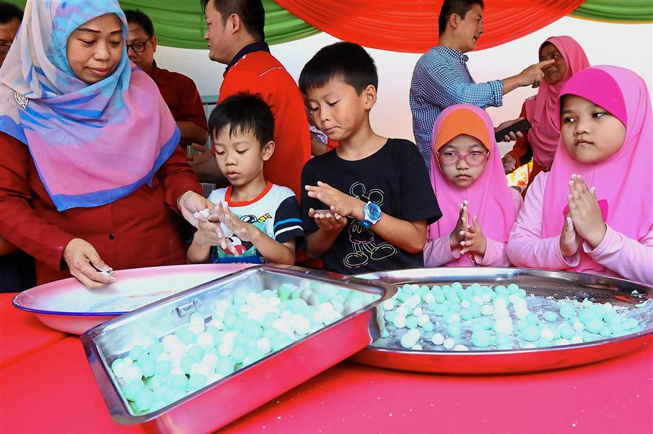 Young kids try their hand at rolling the Tang Yuan during the Dhongzhi Festival at Titi Papan Chinese Mosque in Jalan Burmah.StarPic By: ZAINUDIN AHAD / The Star / 22 Dec 2018
