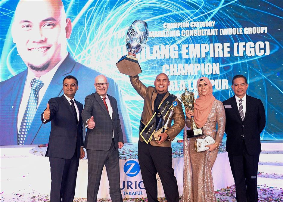 A proud Mohd Fahmi with his wife Tengku Mariam after bagging awards at the Night of the Takaful Stars. With them are (from left) Life Insurance and Family Takaful general manager Mukesh Dhawan, Zurich Life Insurance Malaysia Berhad CEO Philip Smith and Zurich Takaful Malaysia Berhad chief executive officer Salim Majid Zain.