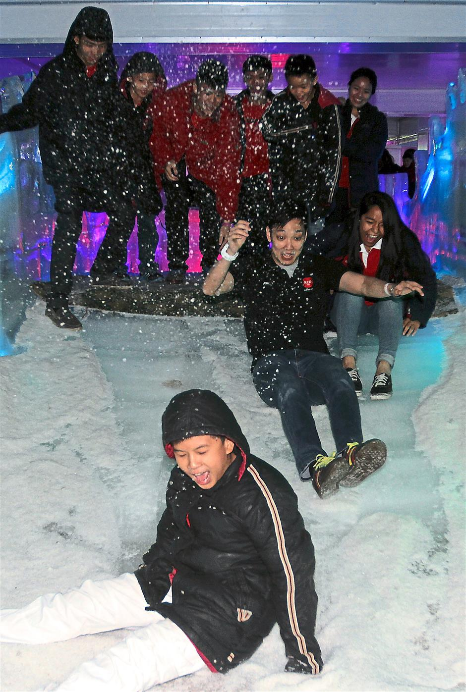 Slippery ice: Red FM's Jeremy (second from right) joining in the fun of sliding down a snowy edge at the Snowalk.