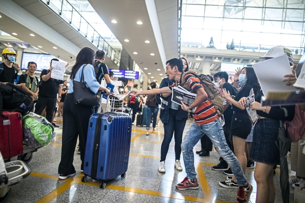 A demonstrator hands a leaflets to a traveler in the arrival hall during a protest at Hong Kong International Airport in Hong Kong, China, on Friday, July 26, 2019. Hundreds of protesters staged a sit-in at Hong Kongu2019s main international airport terminal on Friday, the first of three straight days of demonstrations after clashes last week triggered fears that a wider confrontation could erupt in the Asian financial hub. Photographer: Justin Chin/Bloomberg