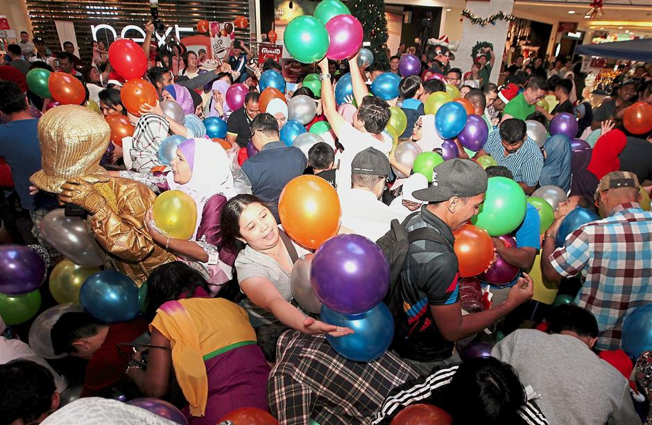 Shoppers collecting as many balloons as they can during the 10,000 Big Points Balloon Drop at the Main Atrium of Quill City Mall Kuala Lumpur.