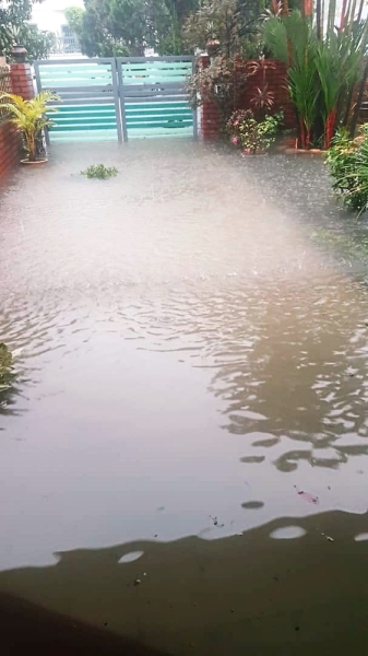 A resident's home along Jalan Putra 5 that was flooded during a downpour. (Right) The underground flood retention pond is located beneath a green space along Jalan Nirwana 46.