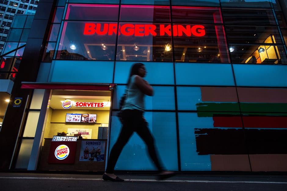 A pedestrian passes in front of a Burger King do Brasil restaurant on Paulista Avenue in Sao Paulo, Brazil, on Monday, Dec. 11, 2017. Burger King do Brasil may raise as much as 2.5 billion reais ($770 million) in its initial public offering if the shares are sold at the top of the target price range of 14.5 to 18 reais, according to O Estado de Sao Paulo. Photographer: Victor Moriyama/Bloomberg