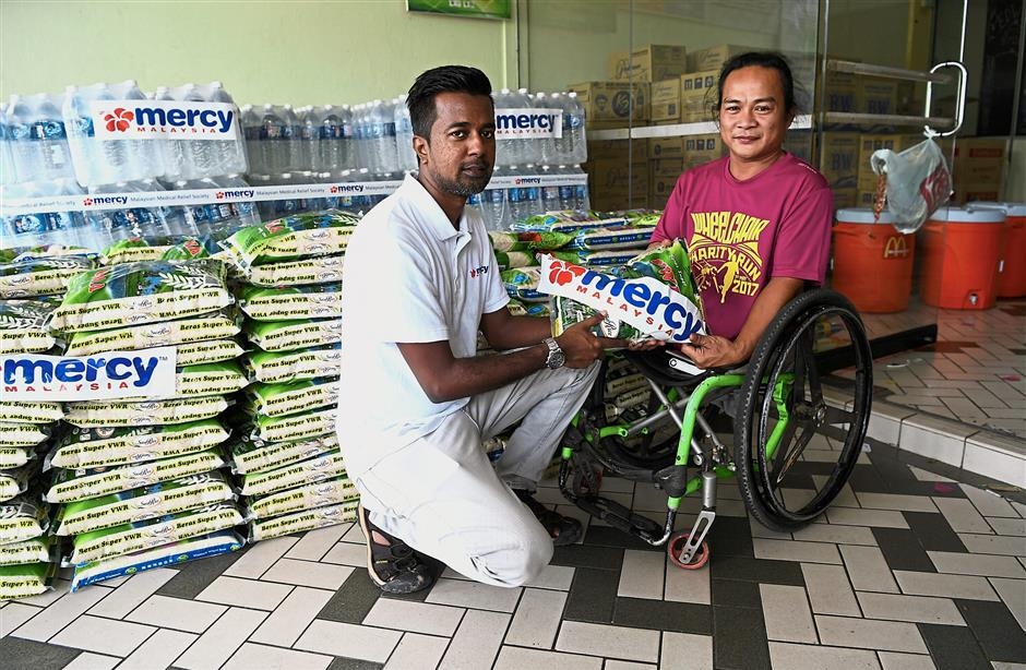 KOTA KINABALU, 3 Jun -- Ketua Misi Mercy Malaysia Sabah Dr Anbarasu Ramalingam (kiri) menyampaikan sumbangan seorang sukarelawan Orang Kurang Upaya yang juga mangsa banjir Penampang Francis Xavier Kinjin, 33, di Kompleks Sukan Penampang hari ini.Mercy turut menghantar bantuan makanan dan minuman kepada mangsa-mangsa banjir di Penampang yang teruk dilanda banjir kilat pada 31 Mei lepas.--fotoBERNAMA (2018) HAK CIPTA TERPELIHARA