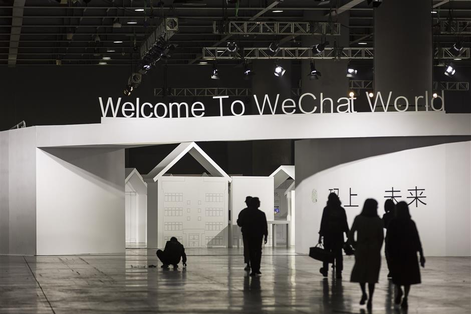 Attendees walk past signage at Tencentu00a0Holdings Ltd.\'s WeChat Open Class Pro conference in Guangzhou, China, on Monday, Jan. 15, 2018. WeChat, the social network that is nearly ubiquitous in China,u00a0said at the conference that it has 580,000 mini-programs in operation. Photographer: Qilai Shen/Bloomberg
