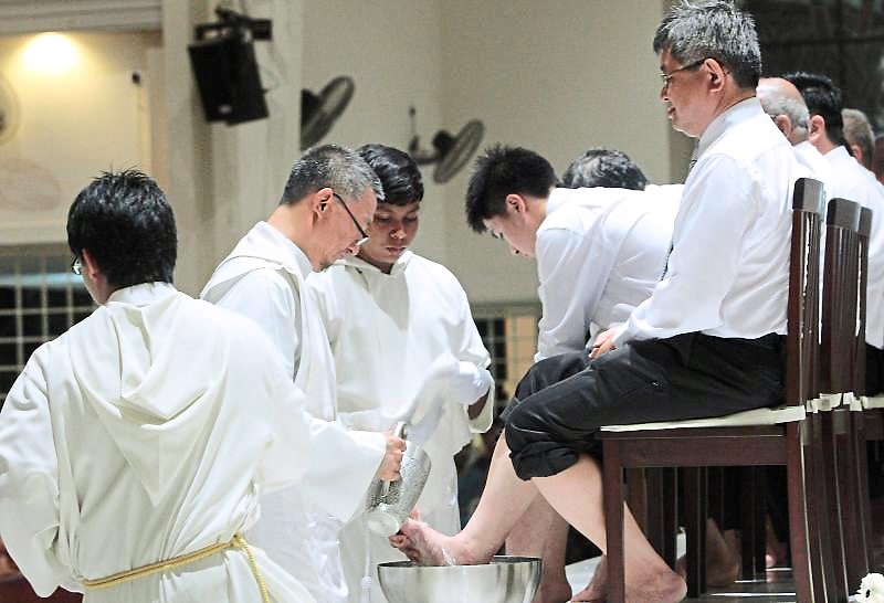 Duty to serve: Father Simon Yong washing the feet of several men at the Church of St Francis Xavier for Maundy Thursday mass previously. On Maundy Thursday, twelve men from the congregation volunteer to participate in the washing of feet, which commemorates what Jesus did for his twelve apostles at the Last Supper. – filepic