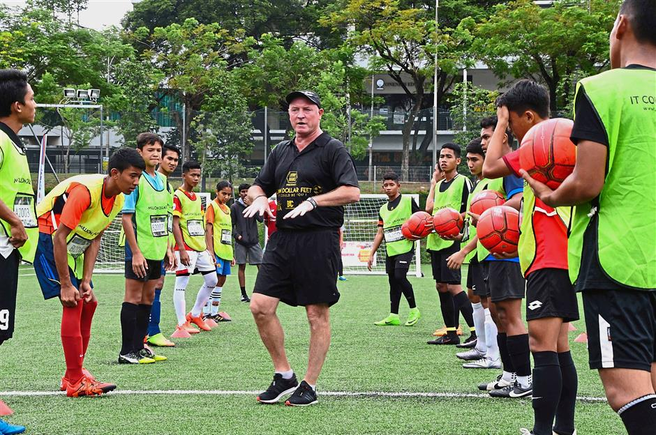 Former Liverpool captain and Million Dollar Feet head coach Steve McMahon (centre) briefing the 14 finalists as they get ready for their final test during the grand finals in October.