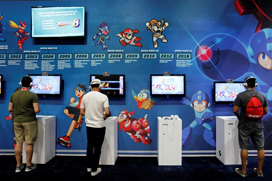 FILE PHOTO: Attendees play video games at E3, the world's largest video game industry convention in Los Angeles, California, U.S. June 12, 2018. REUTERS/Mike Blake - RC1A59673C80/File Photo