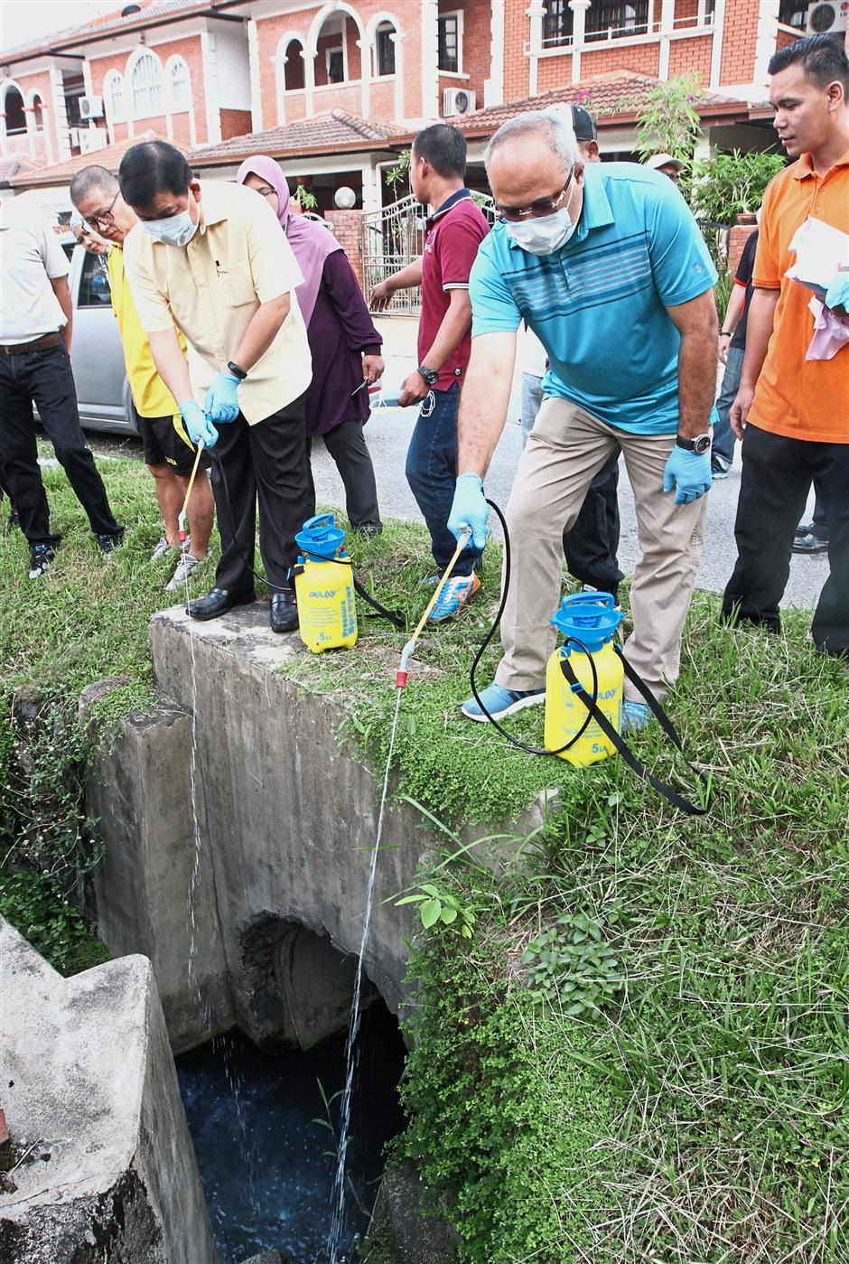 Hee (left) and Mohd Sayuthi spraying larvicide into the drains around Bandar Sungai Long Section 4.
