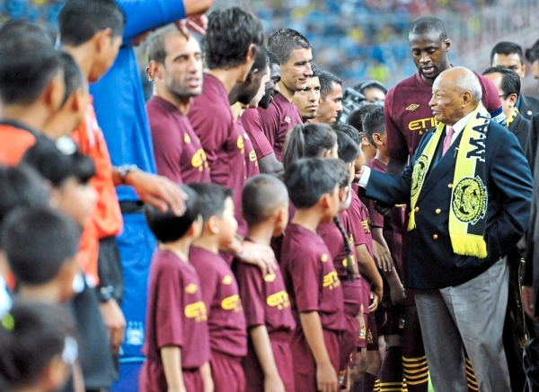 Sultan Ahmad Shah being introduced to Manchester City players by team captain Yaya Toure when the Citizens played a friendly match against Malaysia at the National Stadium in Bukit Jalil. u2014 Filepic