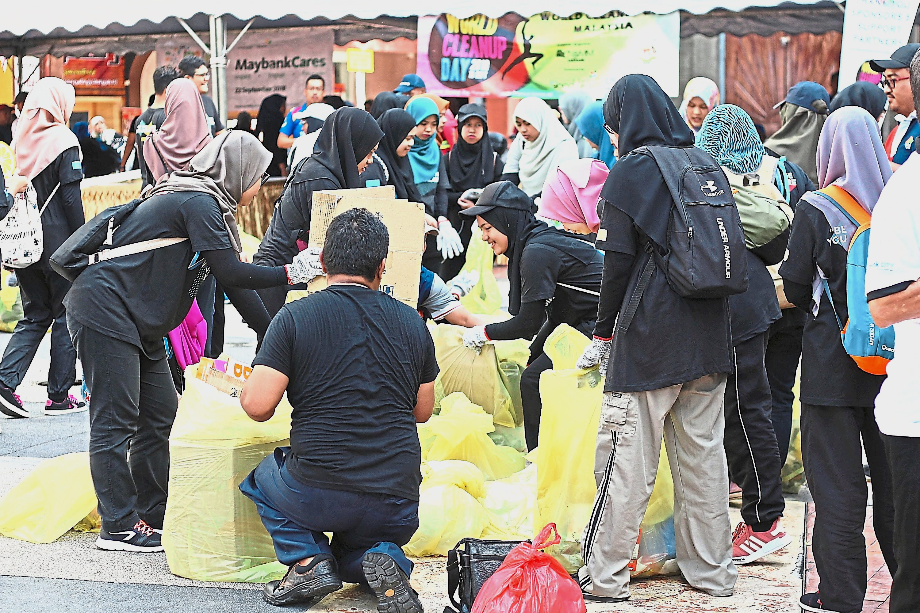 (Left) World Clean-Up Day volunteers collating the collected rubbish for weighing and recycling.