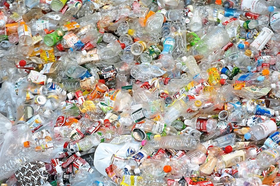 Detailed:Unsorted recyclable materials, including plastic bottles made of polyethylene terephthalate (PET), steel and aluminium cans sit in a pile as they wait to be processed at the Tsurumi Recycling Center in Japan — filepic
