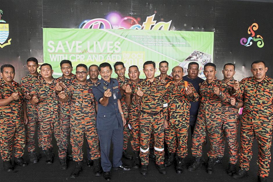 (Above) Dr Afif stressing the importance of the automated external defibrillator in saving lives. (Left) Firefighters posing for a photograph after the state-level Mass CPR-AED launch.