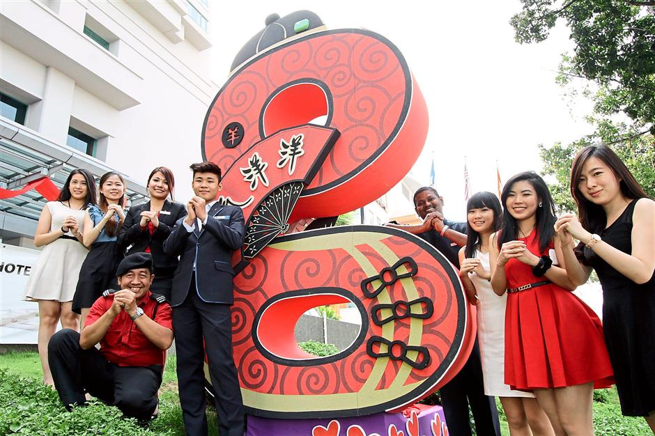 Welcoming the new year: G Hotel Gurney staff members wishing everyone a Happy Chinese New Year alongside their giant G sign, dressed up in traditional attire.