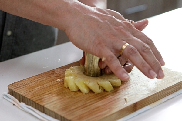 The pineapple's skin and eyes are removed first before being sliced into rings and before removing the core.