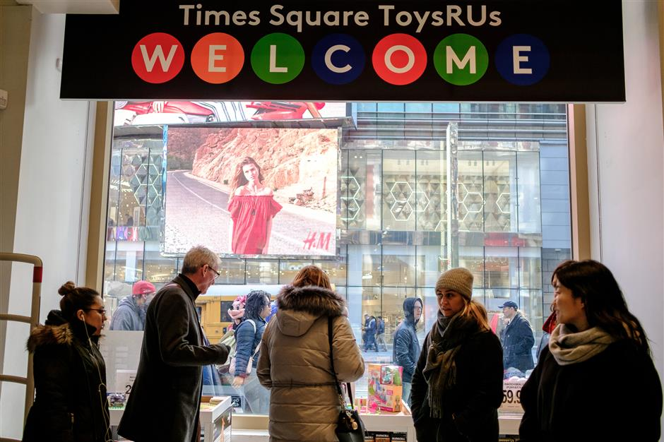 Customers view merchandise displayed for sale at a Toys R Us Inc. retail store at Times Square in New York, U.S., on Thursday, March 15, 2018. Toys \'R\' Us Inc., the ultimate toyland for baby boomers and their kids, is going out of business after a failed rescue effort, unable to recover from intense competition and crushing debts. Photographer: Christopher Lee/Bloomberg