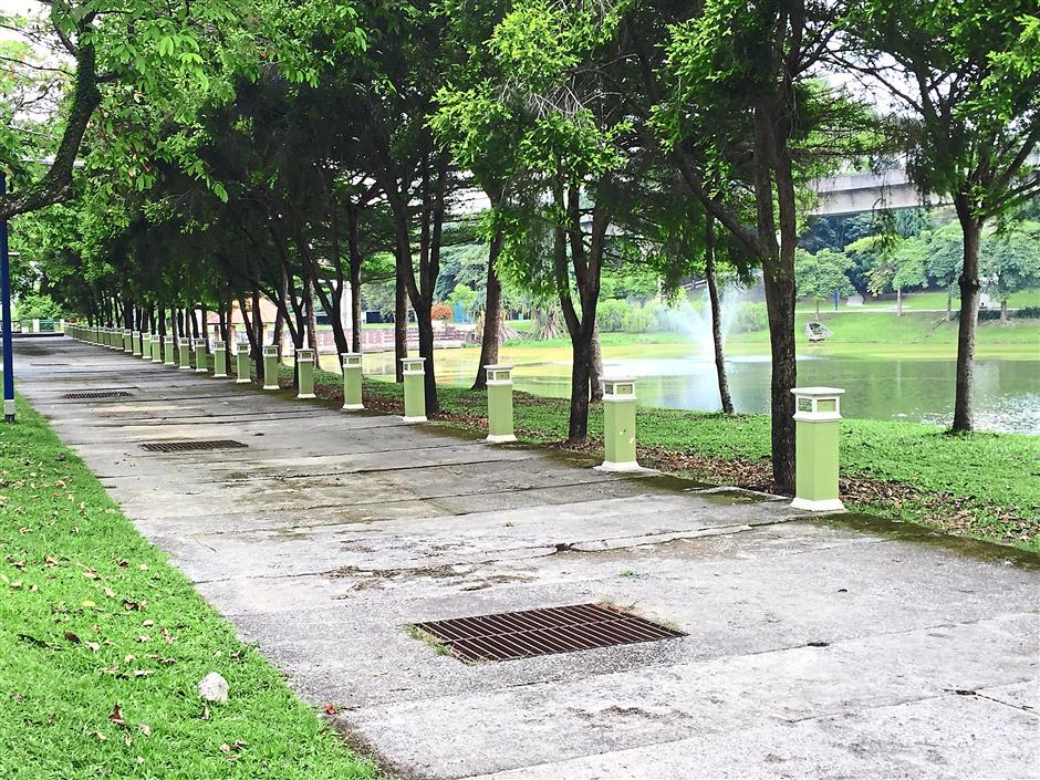Hazardous: The metal-covered drains and uneven jogging path at Taman Aman