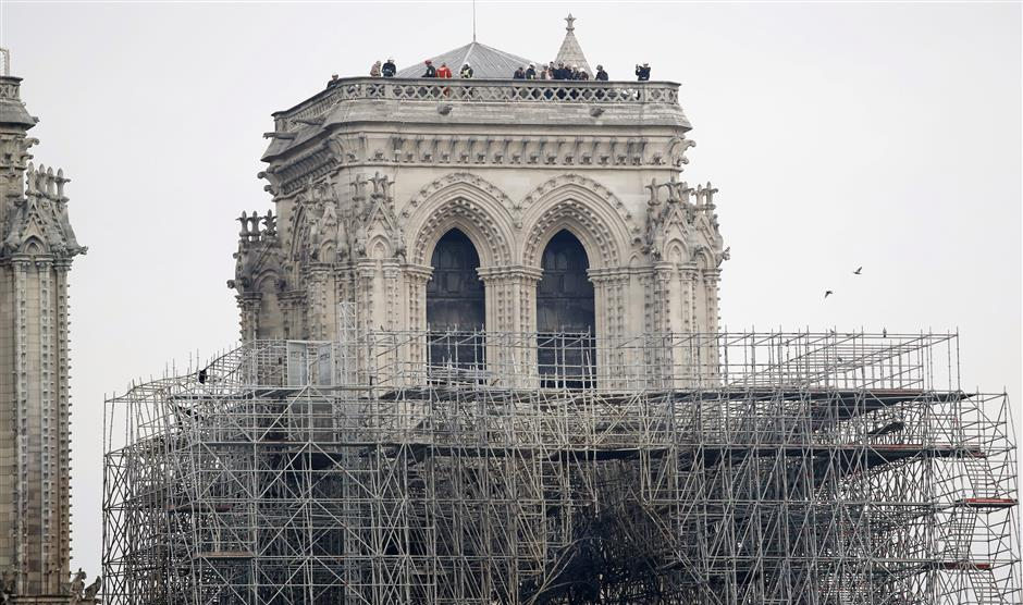 Firemen inspect the Notre Dame cathedral after the fire in Paris, Tuesday, April 16, 2019. Experts are assessing the blackened shell of Paris\' iconic Notre Dame cathedral to establish next steps to save what remains after a devastating fire destroyed much of the almost 900-year-old building. With the fire that broke out Monday evening and quickly consumed the cathedral now under control, attention is turning to ensuring the structural integrity of the remaining building. (AP Photo/Christophe Enaa)