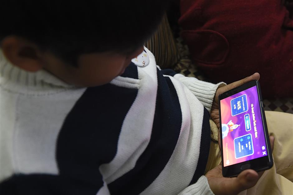 In this photograph taken on February 13, 2019, an Indian boy uses a smartphone to study with an app created by Planet Sparks that uses 'gamified' teaching methods at a tuition centre in New Delhi. - From a multi-billion-dollar education startup to wired-up mannequins, technology is helping to revolutionise the way Indian schoolchildren are learning -- provided their parents can afford it. (Photo by Money SHARMA / AFP) / To go with 'INDIA-ECONOMY-EDUCATION-TECHNOLOGY-AMAZON-BYJU',FOCUS by Vishal MANVE