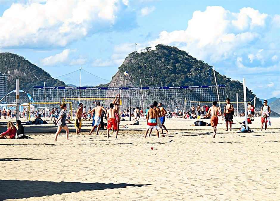 Locals and tourists playing beach volleyball at the Copacabana in Rio.