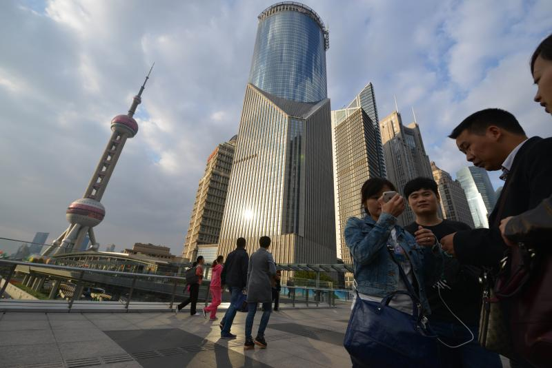 Visitors pose for pictures in the financial district of Shanghai on October 16, 2013. China\'s economy is set to grow 7.6% in 2013, surpassing the government\'s 7.5% target - AFP Photo.