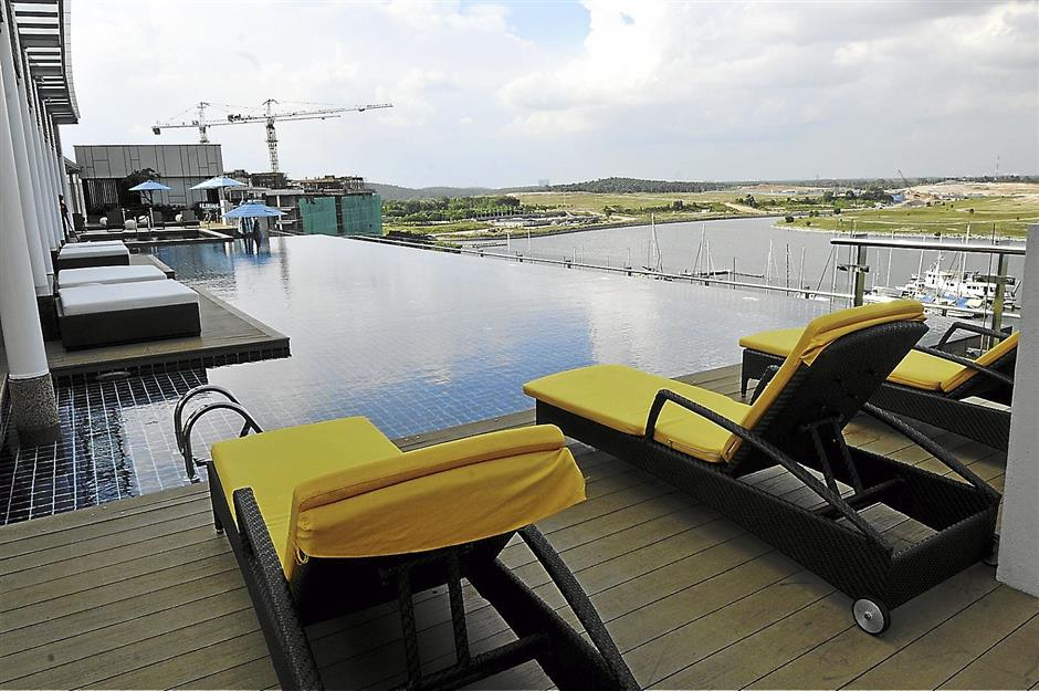 Amazing view: Guests can kick back and enjoy the waterfront view from the deck chairs at Traders Hotel Puteri Harbour's rooftop infinity pool next to their Sky Bar.