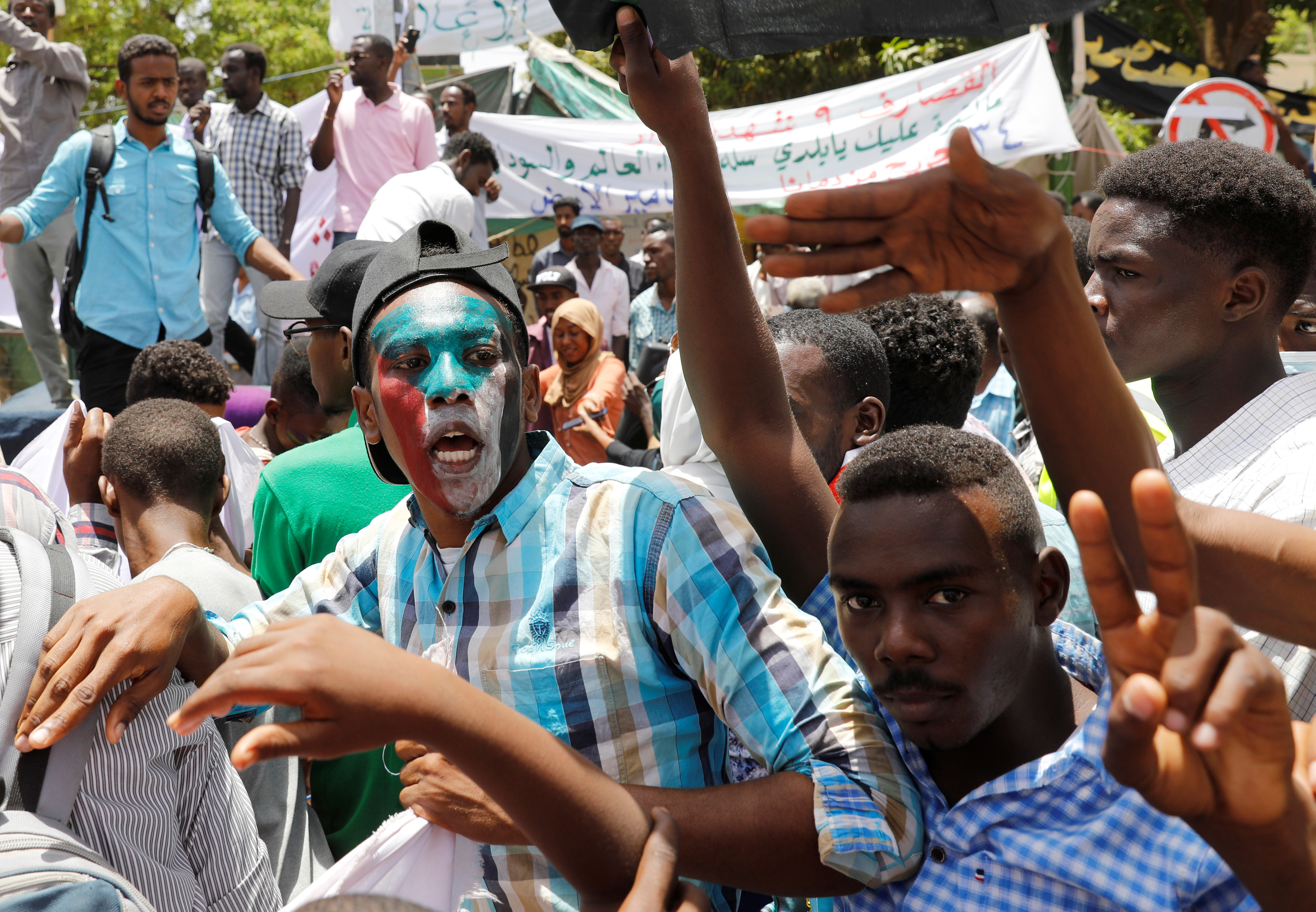 Protesters make victory signs and shout slogans in front of the Defence Ministry in Khartoum, Sudan, April 20, 2019. REUTERS/Umit Bektas