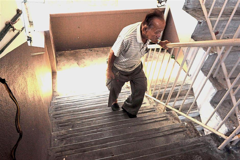 An elderly resident making an arduous climb up the staircase at the Kedah Road flats after all the four lifts broke down simultaneously.